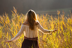 Girl with tattoo mountains on the shoulder standing and meditating in field of reeds / Blond girl walking through field of reeds Royalty Free Stock Image