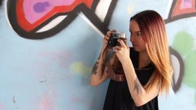 Girl with tattoo and vintage camera near the graffiti wall and photographs. stock video