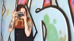 Girl with tattoo and vintage camera stand near the graffiti wall. stock video footage