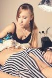 Girl tattooer master portrait during creation tattoo on a tummy. Stock Photo