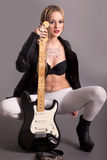 Girl with tattoos posing with a guitar Royalty Free Stock Photos