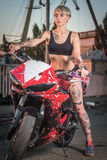 Girl with tattoos sitting on a motorcycle Stock Photo