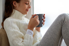 Girl with tea mug sitting at home window. Hot drinks and people concept - beautiful girl in winter sweater with tea mug sitting at home window Stock Image