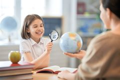 Girl with teacher in classroom. Back to school. Happy child is sitting at desk. Girl with teacher in classroom royalty free stock photo