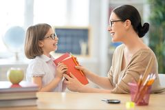 Girl with teacher in classroom. Back to school. Happy child is sitting at desk. Girl with teacher in classroom stock photography
