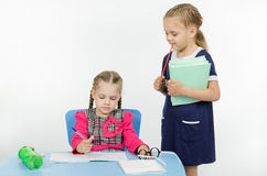 Girl teacher enthusiastically looking at the notebook student Royalty Free Stock Photo