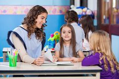 Girl With Teacher And Friend In Classroom Stock Image