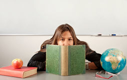 Girl teacher hiding behind book Stock Image