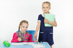 Girl teacher points at student notebook Stock Photo