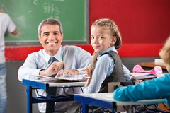 Girl And Teacher Sitting At Desk In Classroom. Portrait of little girl and teacher sitting at desk in classroom Royalty Free Stock Images