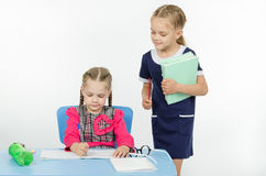 Girl teacher during task checks correctness of its implementation Royalty Free Stock Images