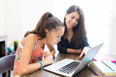 Girl And Teacher Using Laptop At Table. Girl and teacher using laptop during homeschooling at table royalty free stock photos