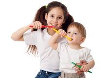 Girl teaches boy brushing teeth Stock Image