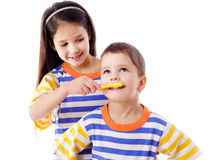 Girl teaches a boy to brush your teeth Stock Photo