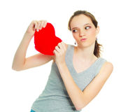 Girl tearing a heart-shaped pillow Stock Photo