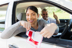 Girl tearing L sign. Happy girl sitting in a car tearing a L sign after getting her driver's license stock photo