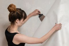 The girl tears off the old wallpaper from the concrete wall and holds a spatula. royalty free stock images