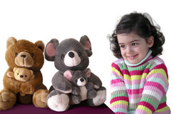 Girl and Teddies. Pretty little girl in shy expression, wishing to have two teddy bears Royalty Free Stock Image