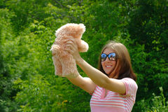 Girl and teddy. The girl on a meadow in the sun glasses, having control over a toy bear Stock Images