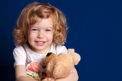 Girl with teddy bear. Laughing girl embraces teddy bear royalty free stock photo