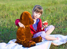 Girl with teddy bear. In a meadow. best friends Stock Photos