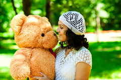 Girl with teddy bear. Smiling young girl looks at the teddy bear Stock Photo