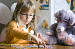 Girl and teddy bear. A cute young girl together with her teddy bear, arranging jigsaw puzzle Stock Images