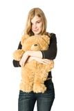 Girl with a Teddy bear. Young girl hugging a teddy bear, isolated Royalty Free Stock Image