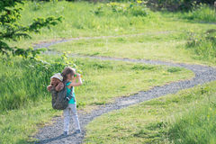 Girl with teddy bear in backpack looking at the trail ahead Royalty Free Stock Images