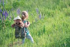 Girl with teddy bear in backpack in tall grass Royalty Free Stock Image