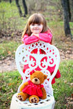 Girl with a teddy bear and a chair in the forest Royalty Free Stock Image