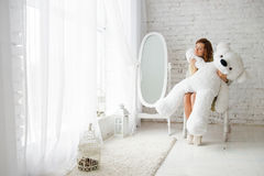 Girl and teddy bear. Concept of tenderness, love card. Autumn day, joy of gifts. Attractive girl sitting on chair and embraces a large polar bear in a white room royalty free stock image