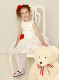 Girl with Teddy bear. Cute little girl in white dress sitting on a white chair . The girl holds the head of a large Teddy bear Royalty Free Stock Photo