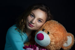Girl with a teddy bear on a dark background Royalty Free Stock Image