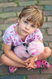 Girl with teddy bear. A little girl with a teddy bear sitting on a pavement Royalty Free Stock Image