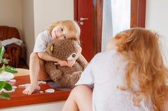 Girl with teddy bear looking through near mirror Stock Image