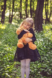 Girl with teddy-bear. Lovely girl in black dress holding teddy bear toy in the spring forest Stock Image