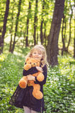 Girl with teddy-bear. Lovely girl in black dress holding teddy bear toy in the spring forest Stock Photos