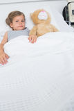 Girl with teddy bear lying in hospital bed Royalty Free Stock Photo