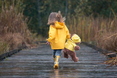 Girl with teddy bear in matching yellow raincoats running in the. Happy girl and her teddy bear in matching yellow raincoats having fun in the rain royalty free stock photography
