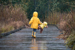 Girl with teddy bear in matching yellow raincoats walking in the. Happy girl and her teddy bear in matching yellow raincoats having fun in the rain royalty free stock photography
