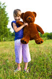 Girl with teddy bear in a meadow. Happy girl with brown teddy bear playing in a meadow. best friends Royalty Free Stock Photography