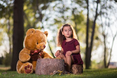 Girl with a teddy bear in the park Royalty Free Stock Image