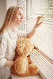 Girl with teddy bear. Sad girl with teddy bear looking in window, toned image Stock Photography