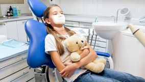 Cute girl with teddy bear sitting in dentist chair in clinic and feeling nervous before treating teeth Royalty Free Stock Images