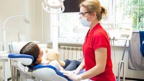 Cute girl with teddy bear sitting in dentist chair before teeth treating. Girl with teddy bear sitting in dentist chair before teeth treating royalty free stock photos