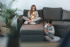 Girl with teddy bear on sofa and boy sitting with arms crossed Royalty Free Stock Photography