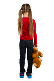 Girl with a Teddy Bear. Girl stands with her back to the viewer, holding a teddy bear stock images