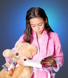 Girl with teddy bear and storybook ready for bed Royalty Free Stock Photos