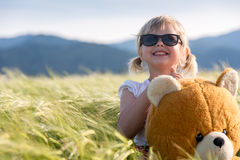 Girl and Teddy bear in a wheat field Stock Image